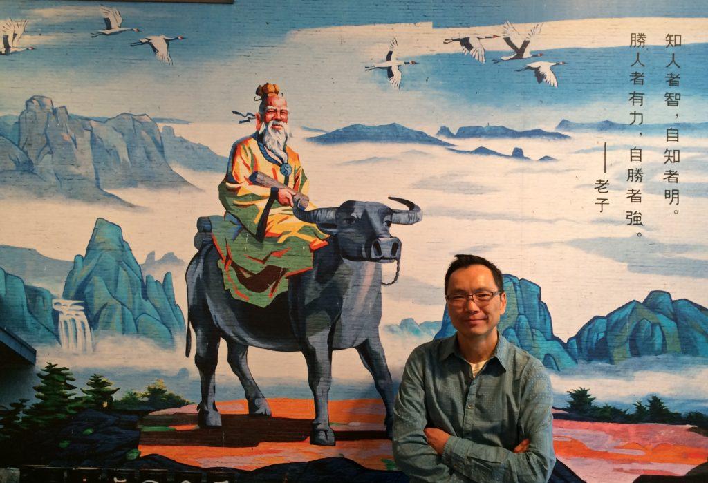 """Wayne Ng in front of Morris Lum's Mural """"Tong Yan Gaai"""